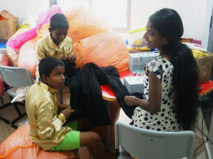 Couple of kids sat amonst SOME of the donated clothes getting their trousers altered